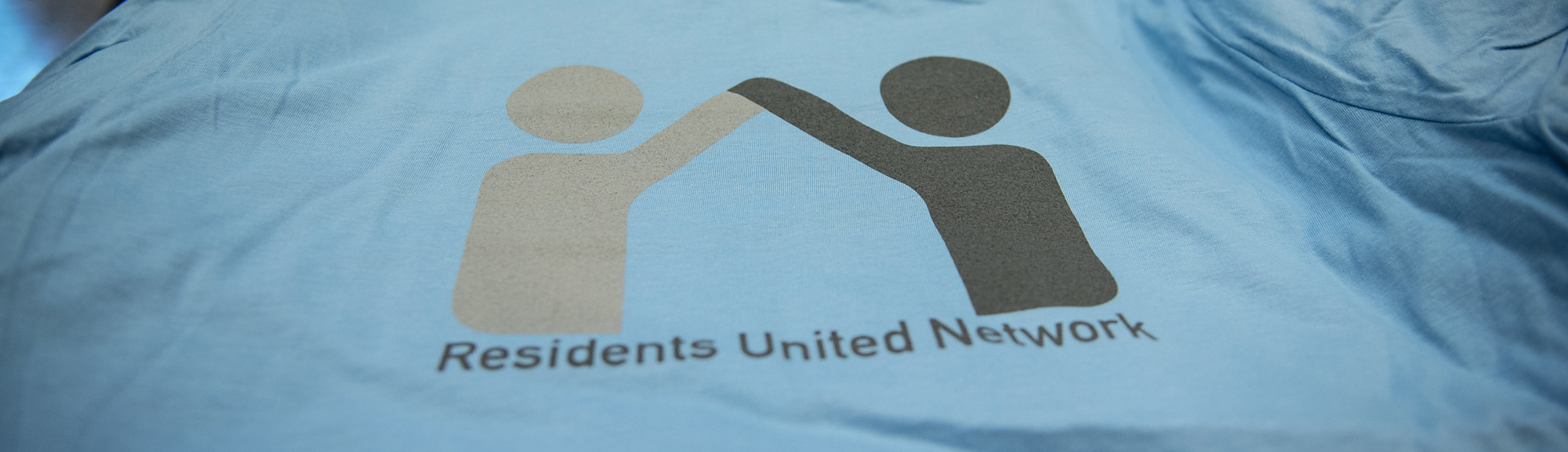 A close-up of a light blue t-shirt with Residents United Network printed on the front.