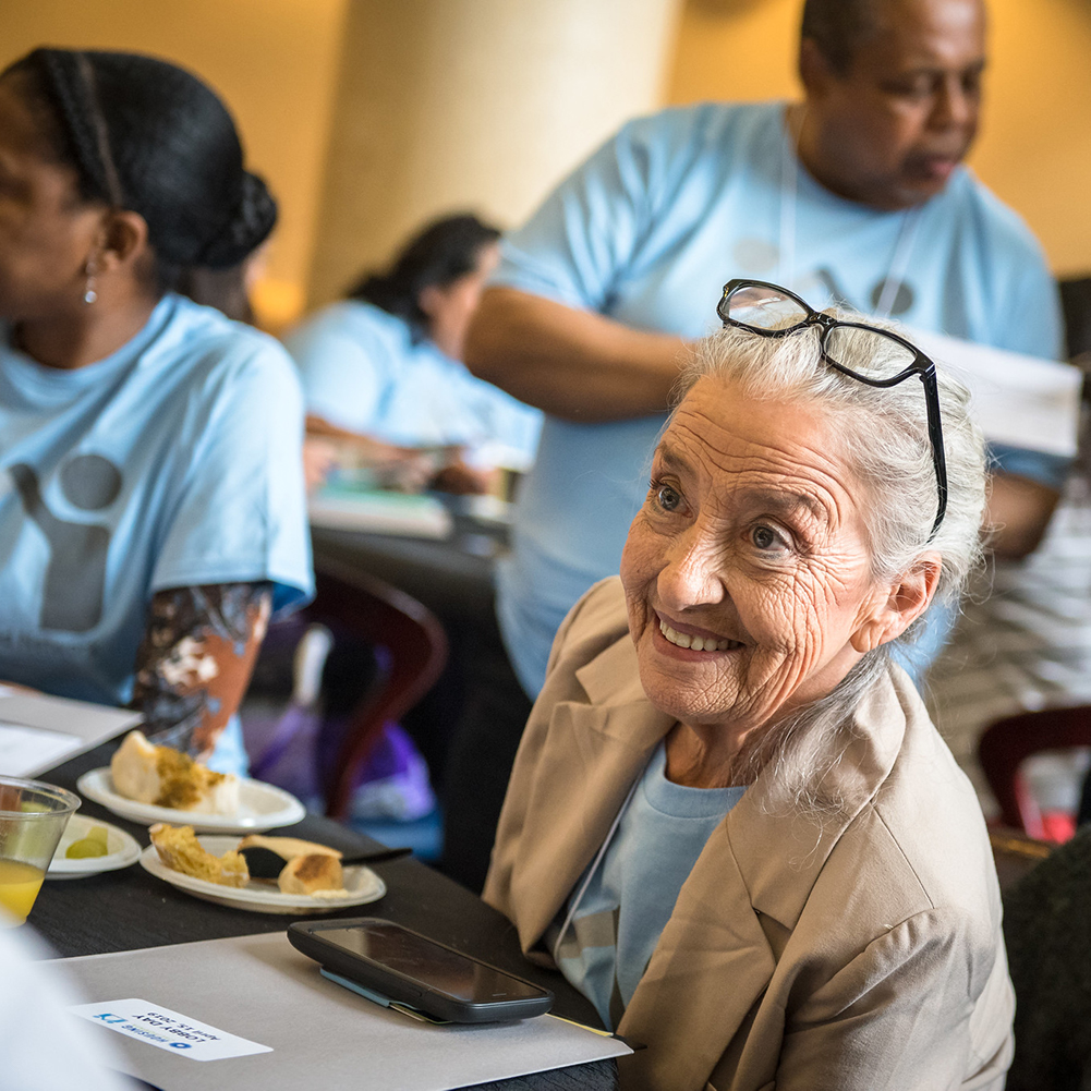 Close-up photo of an elderly white woman in a light blue t-shirt sitting at a table and talking with another Lobby Day attendee off camera. She has white hair, a big smile, and glasses perched on her head.