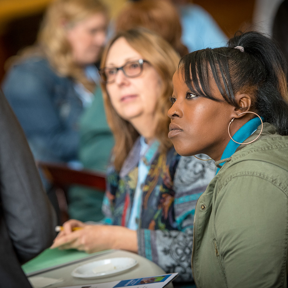 Close-up photo of a young black woman sitting at a table, she is in a room with many other people and listening intently to a speaker.