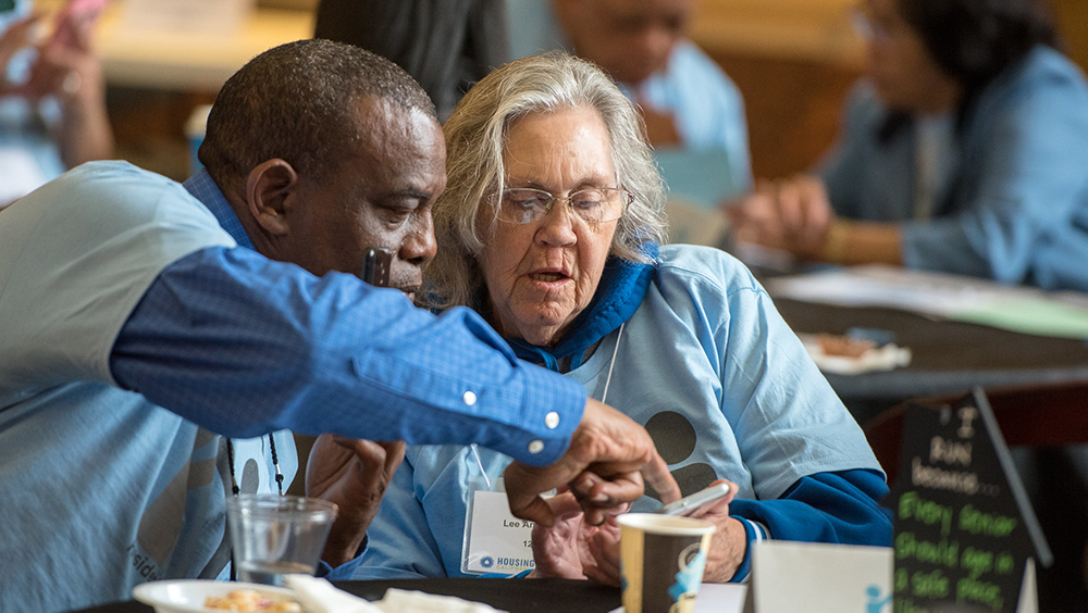 Two seniors, an African American man and a caucasian woman in glasses, study something on the woman's phone. They are wearing light-blue t-shirts and are attending Lobby Days.