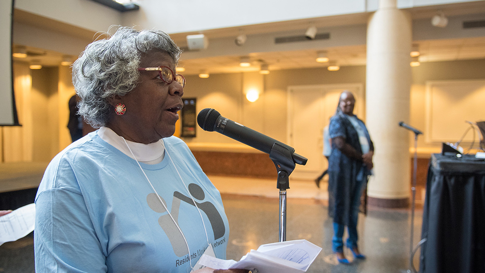 An African American woman with curly gray hair, red-rimmed glasses, and a light blue t-shirt, stands at a microphone. She holds a paper in her hand, her head is held high and she is talking to people off camera to the right of the image.