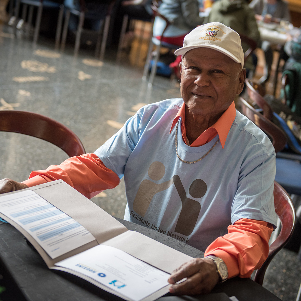 Close-up photo of a senior man in a ball-cap and a light blue t-shirt, sitting at a circular table reading a folder with information about Residents United Network. He is looking at the camera with a slight smile, and is surrounded by lots of other people at tables too. It is Lobby Day for RUN leaders.