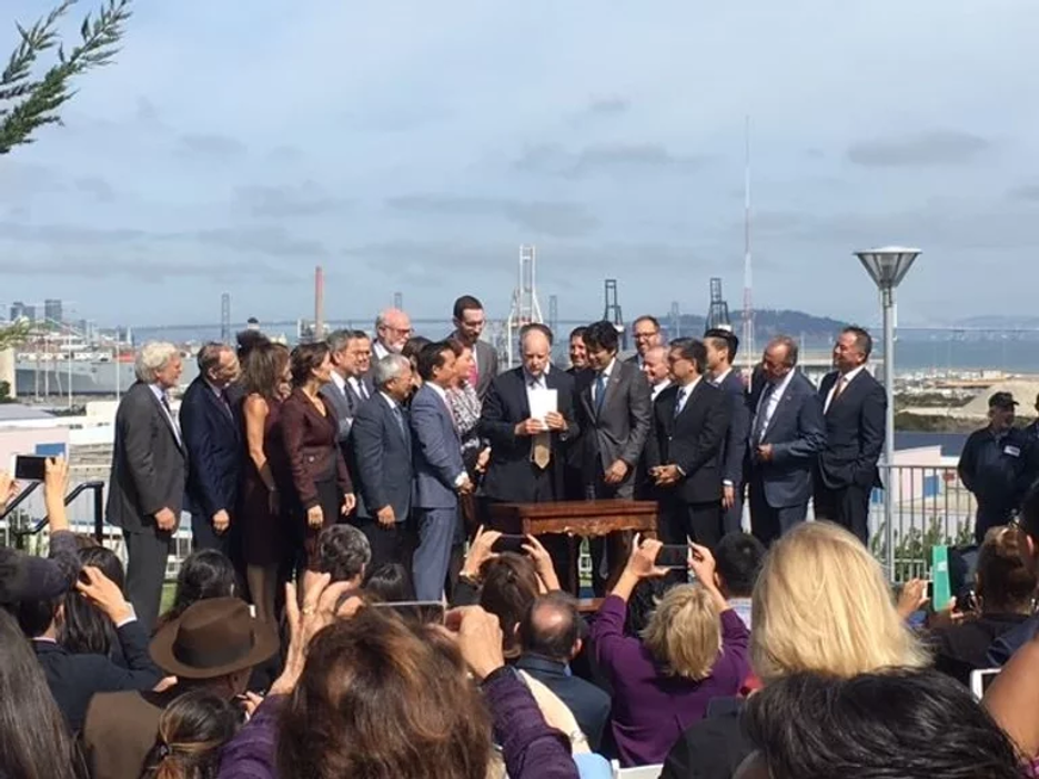 A group of Housing California supporters stands on a raised platform in San Francisco by the water, in front of a crowd. Governor Jerry Brown is on the center of the group, and Housing California Executive Director, Lisa Hershey, is also on the stage. The crowd are taking photographs with their smartphones.