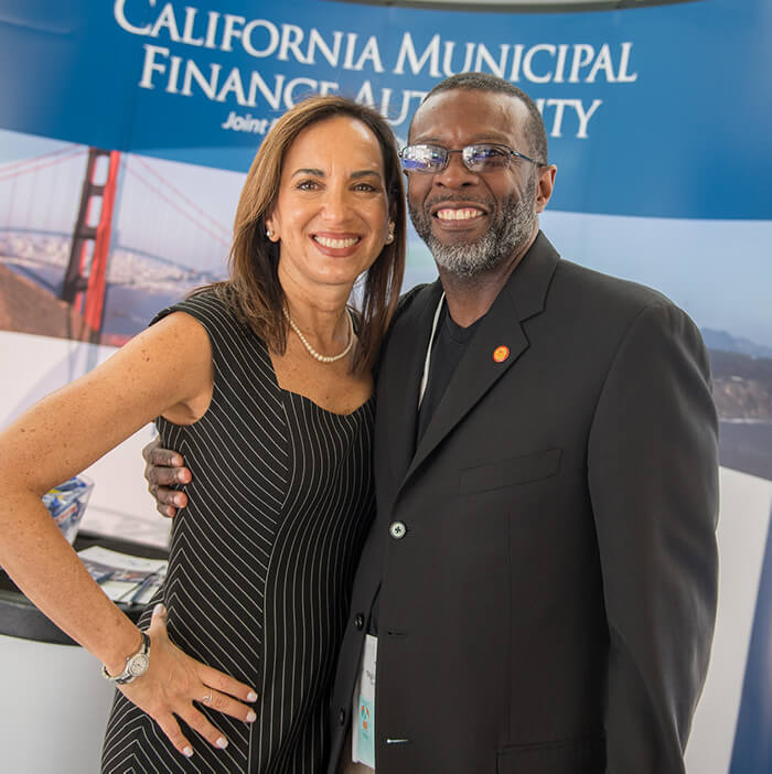 At the Housing California Annual Conference, Executive Director Lisa Hershey smiles for the camera with her arm around a smiling black gentleman in glasses and a suit. They are standing at the supporter booths, and the banner behind them says California Municipal Finance Authority.