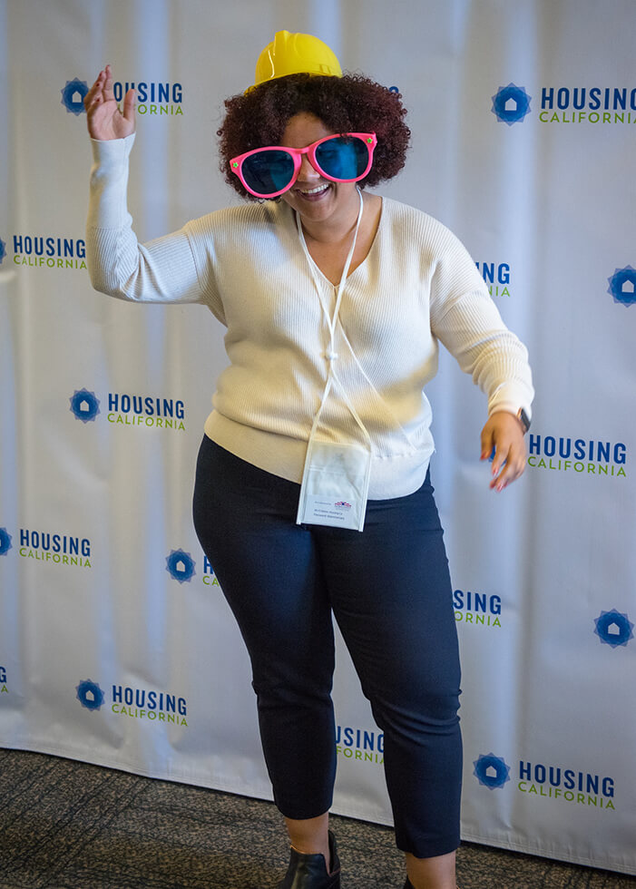 A woman with curly hair strikes a goofy pose at the photo booth. She has one arm in the air and looks like she is dancing. She is wearing a tiny yellow hard-hat and very large pink-rimmed clown glasses. She is having a great time at the Annual Conference!