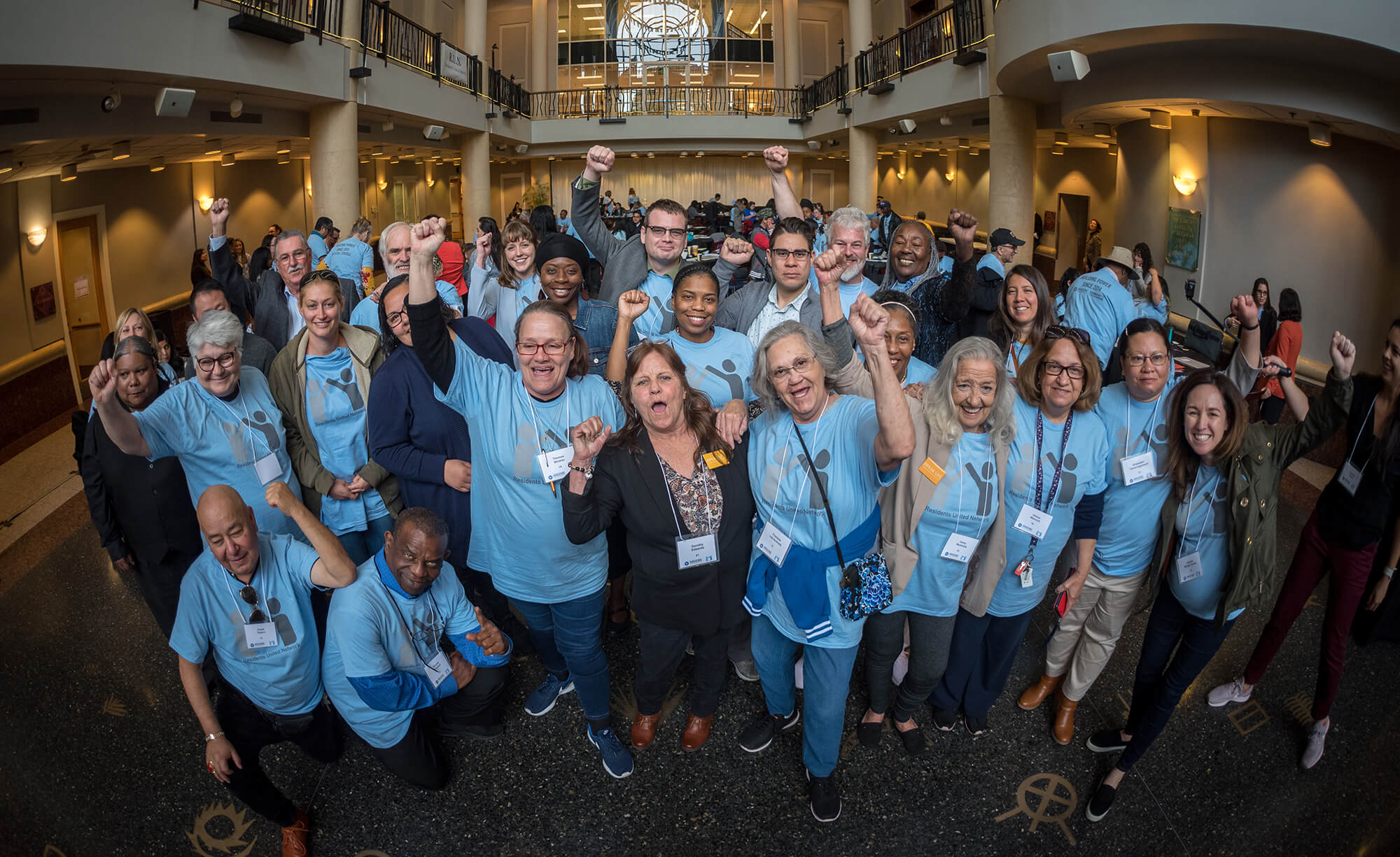 A group of around 30 people are standing inside a large well-lit hall. They are looking at the camera and cheering. Everyone is wearing a light blue t-shirt with Residents United Network on the front. The people are all different ages and ethnicities, and they look accomplished, and powerful.