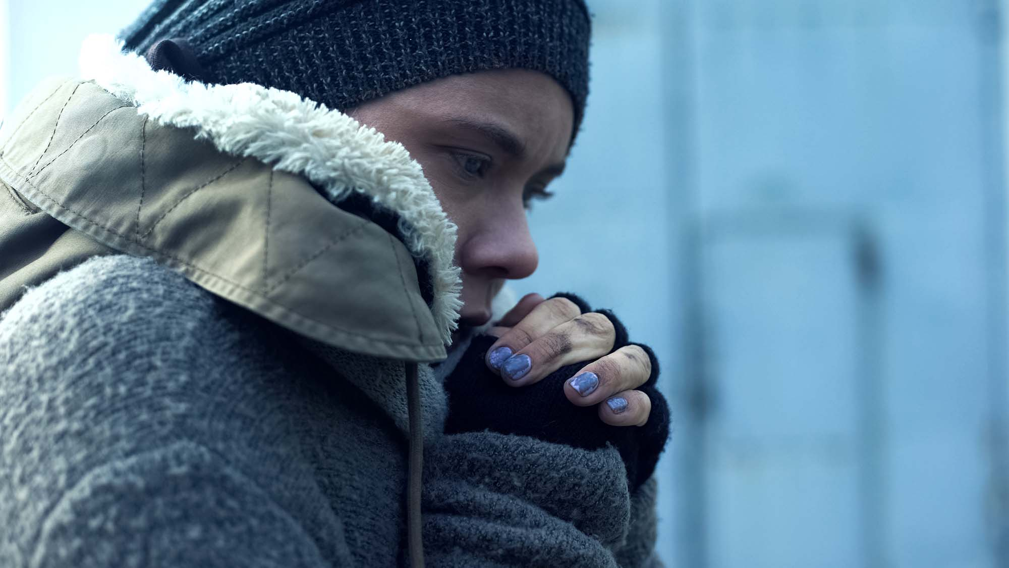 A woman in a knitted hat, fingerless gloves, chipped nail polish, and a large jacket with a furry hood comforts herself in the cold. Her clasped hands are at her chin, and she stares slightly downwards. She appears to be lonely.