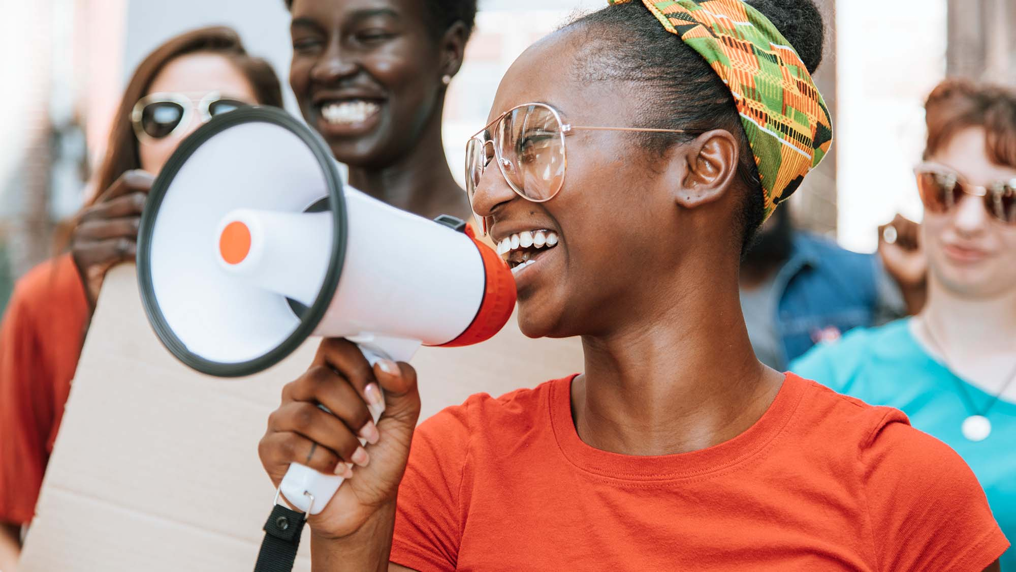 Young African American woman leads a group of people in making their voices heard. They are walking on the street and she has a mega-phone up to her mouth. She is smiling and positive in a colorful headband and red t-shirt.