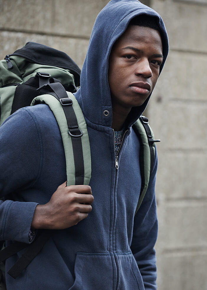 An African American teenage boy stands in front of a large gray wall, his right arm is bent at the elbow and he holds onto the strap of his green backpack. He wears a dark blue hooded sweater. The boy is facing to the right, but his head is looking at the camera, and he looks sad. The concept is homeless youth in California are disproportionately people of color.