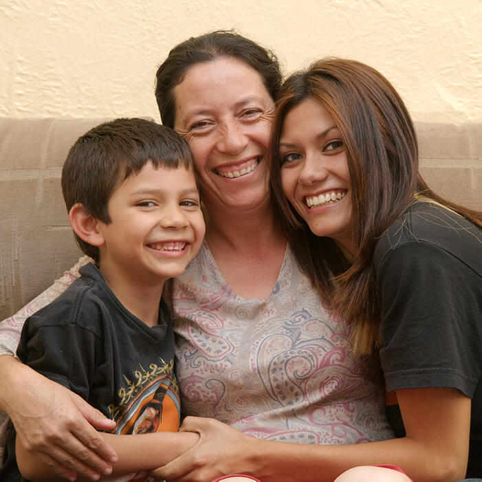 A photo of Maria and her teenage daughter and young son sitting on the couch in their rental home. The children sit on each side of Maria, and she wraps her arms around them. Everyone is smiling at the camera.