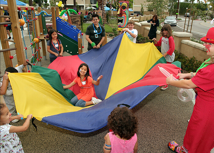 A photo of children playing with a multi-colored parachute in a park connected to affordable apartment homes. They are holding up the parachute while one girl sits in the middle, laughing. The children are very active, smiling and having fun; some of the children have painted faces. A woman dressed as a clown with big shoes and a red bowler hat provides supervision, and laughs with the children.