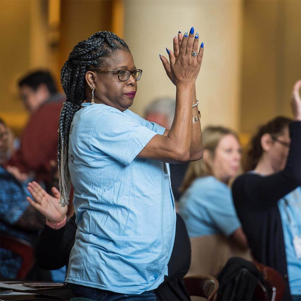 An African American woman with long brown braided hair, wearing brown-rimmed glasses and a light blue t-shirt, stands facing to the right, her hands are raised to the height of her forehead and she is clapping. Her long nails are painted blue to match the Residents United Network brand. She looks confident and proud.