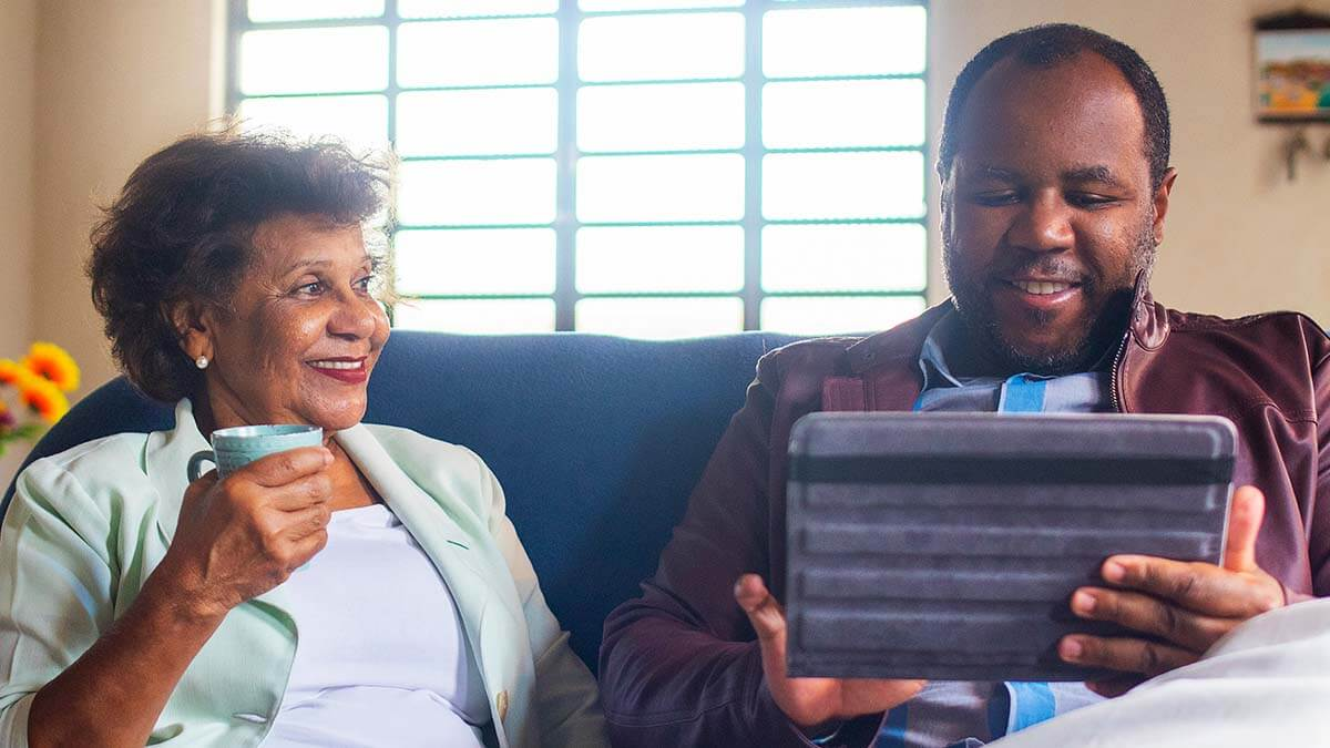 Portrait of a senior mother and her adult son sitting on the couch in front of a bright window. The mother sits on the left, smiling and looking at her son. She is holding a mug. The son is smiling and looking at the digital device he is holding in both hands. They look happy and content in each other's company.