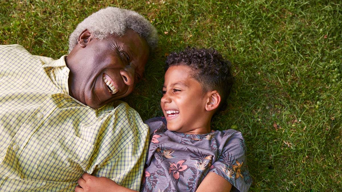 A Grandpa and his young grandson, dressed in bright shirts, lay on their backs on the grass, looking at each other, and laughing.