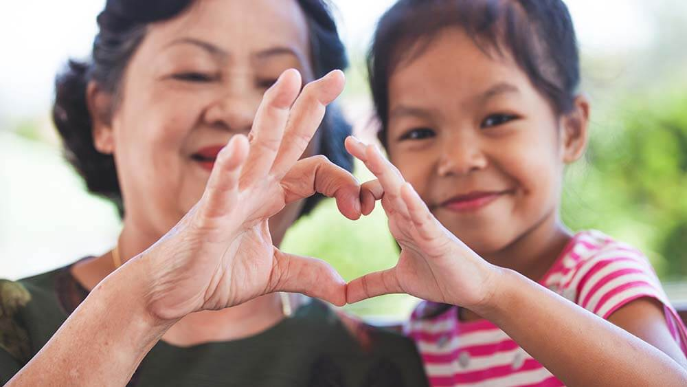 A grandmother and grand-daughter, both of Asian/Pacific Island ethnicity, are shoulder-to-shoulder and facing the camera. Their hands come together in the center, thumbs and forefingers touching and forming a heart shape.