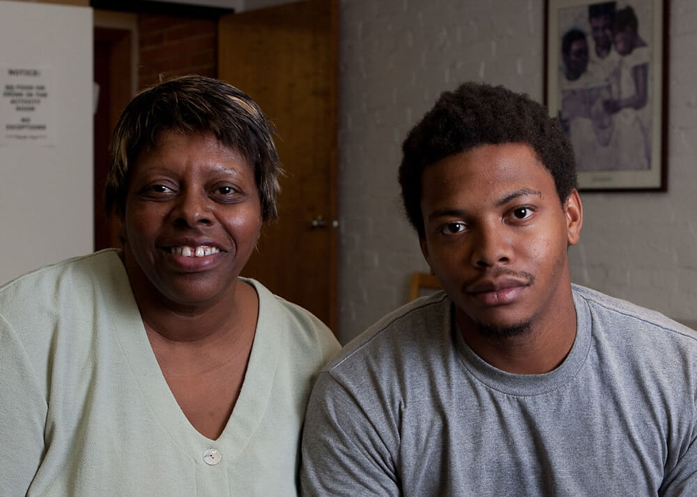 A photo of a mother on the left, and her adult son on the right, they are sitting and looking at the camera. The woman's name is Wenda, and she has been a hard worker and homeowner for most of her life. A series of unexpected medical conditions and bills resulted in Wenda losing her home, and Wenda and her son found themselves on the streets with nowhere to turn. This image was taken the day Wenda received news that she could get temporary accommodation while she looked for a new place to call home. Wenda is smiling, and her son looks relieved.