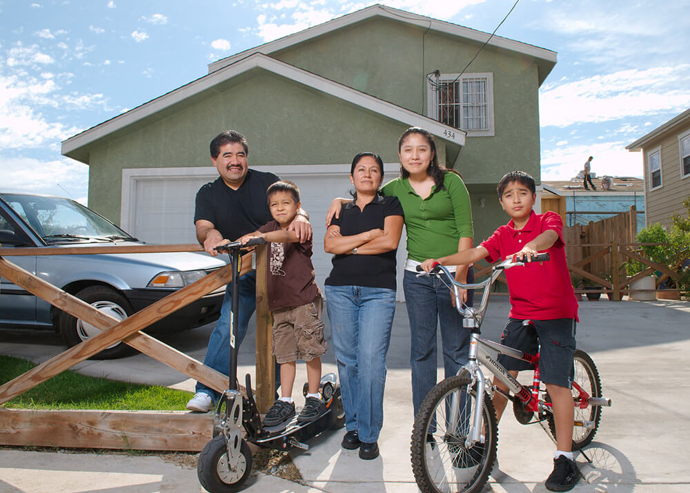 Eufemio and Leticia, Michelle, Alex and Jesse, stand outside their new house in Greater Los Angeles. Alex sits on a bike and his younger brother stands on a scooter. Sandra has her arm around Mom's shoulder. There is a car in the driveway, and in the background two people are standing on roof rafters, they are building a new house. This home is one of several built by homeowners and volunteers with Habitat for Humanity.