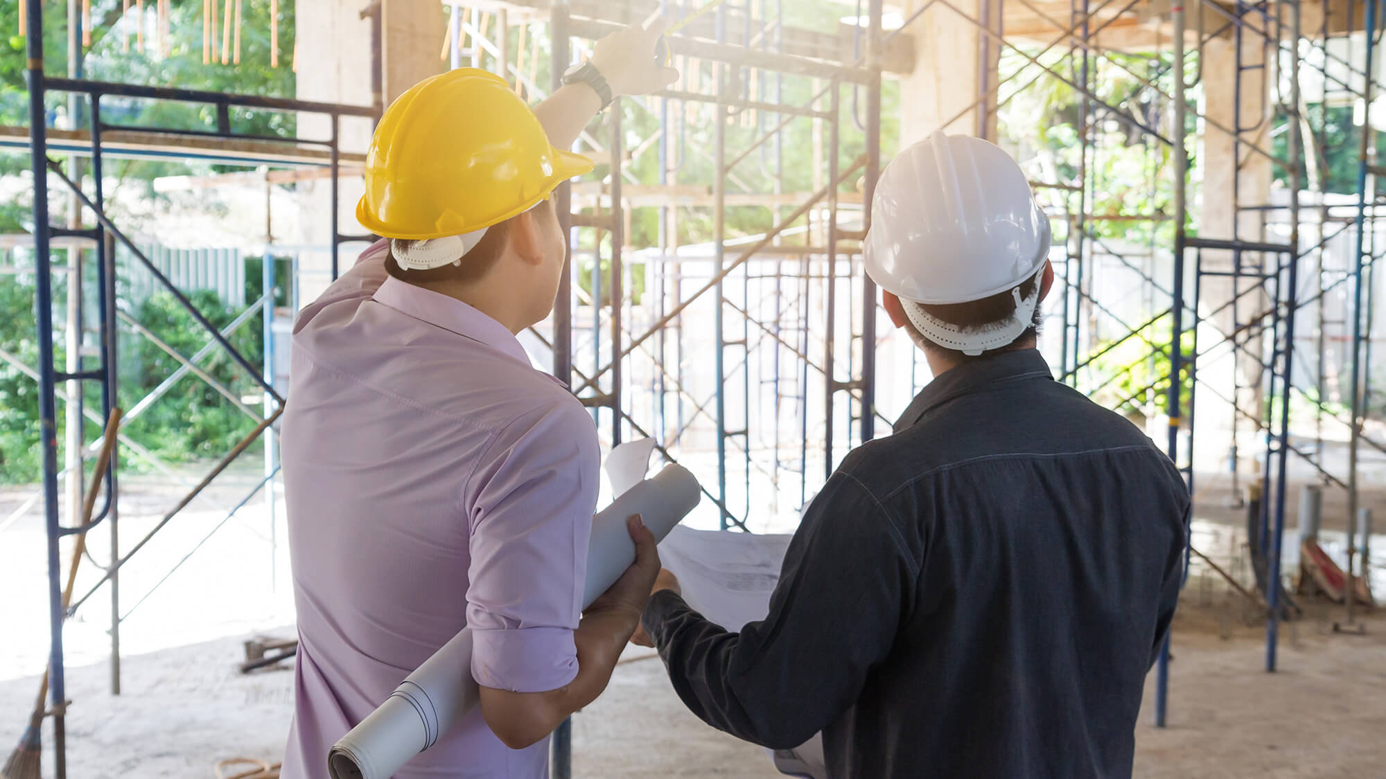 Two people stand on concrete inside scaffolding at a building site. The site is very open and sunny. The people both wear hard-hats and collared shirts. The person on the left, holding rolled plans under their arm, points to the upper levels of the scaffolding. The person on the right holds a plan out in front but looks toward the higher levels, as well.