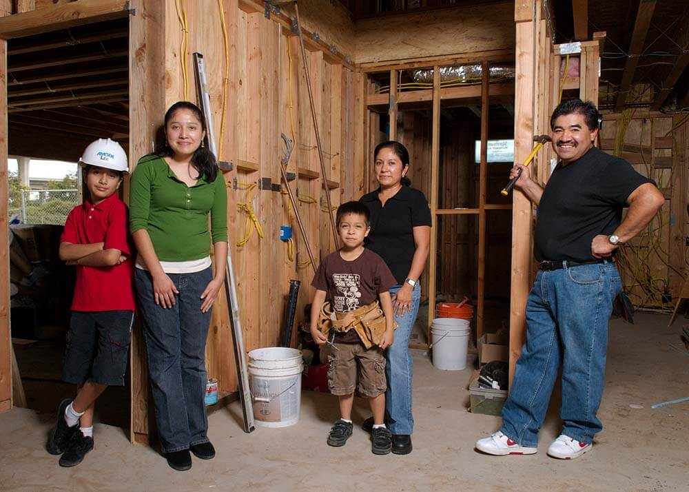 A Latino family stand inside of a partially constructed house. Mom, Dad and three children look at the camera. Dad stands on the right holding a hammer and is smiling. Two young boys wear a tool-belt and a hard-hat, they look confident. There are buckets and wires around them.