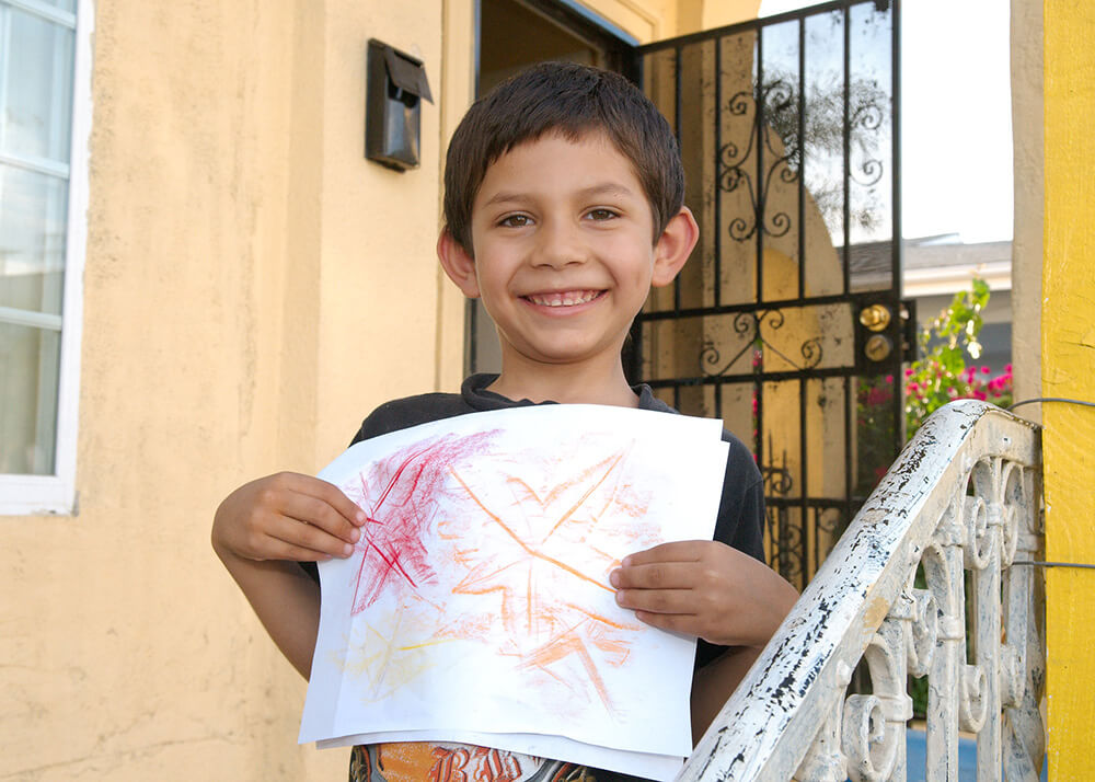This is a photo of a boy named Guillermo. He is a kindergartner and 5 years old. Guillermo is growing up safe and secure with his family in a stable home, where he can do his homework and create art. He is pictured on the steps of his home, he has a huge smile, and he is holding his art in front of him for us to see. He has created leaf rubbings in red, orange, and yellow.